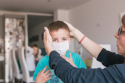mother putting medical mask on her son to protect himself from the coronavirus - p1166m2182902 by Cavan Images