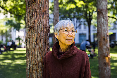 Thoughtful senior woman with gray hair standing by tree at public park - p1166m2285619 by Cavan Images