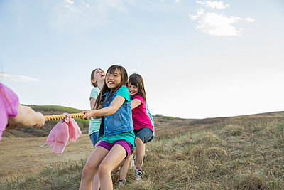 Schoolgirls playing tug-of-war during field trip - p1192m1044074f by Hero Images