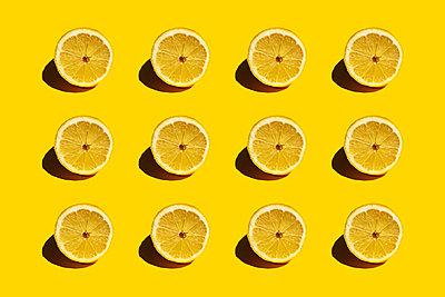 Pattern of fresh halved lemons against yellow background - p300m2198248 by Gemma Ferrando