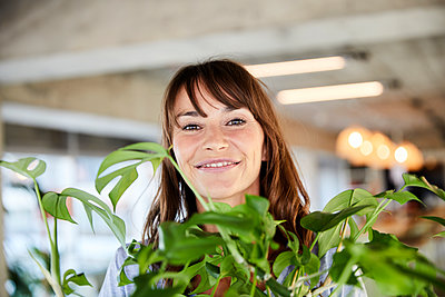 Mature woman holding potted plant at home - p300m2220858 by Jo Kirchherr