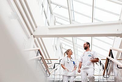 Doctors talking on hospital corridor - p312m2174707 by Scandinav