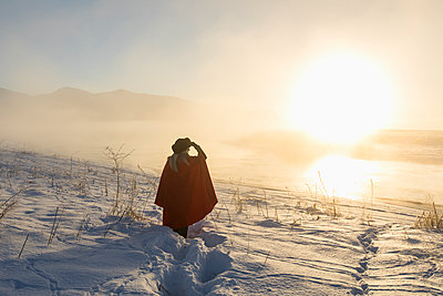 Caucasian woman shielding eyes in winter landscape at sunset - p555m1232041 by Steve Smith