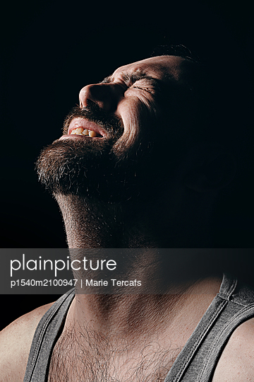 Bearded man with a suffering expression on a black background  - p1540m2100947 by Marie Tercafs