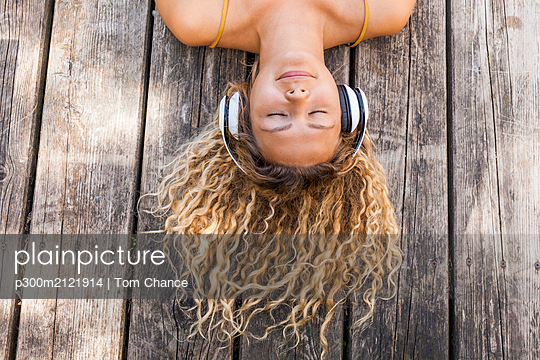 Smiling woman listening to music, lying on wood - p300m2121914 by Tom Chance