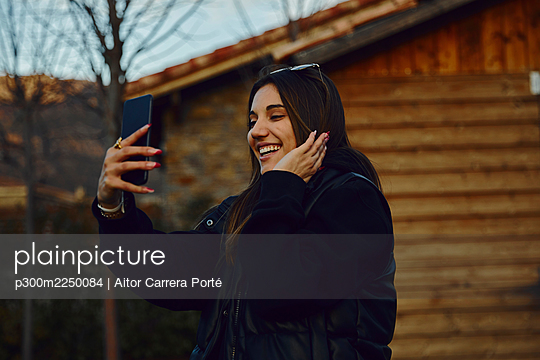 Happy young woman taking selfie through mobile phone by house - p300m2250084 by Aitor Carrera Porté