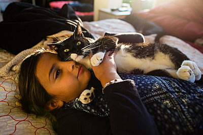 Girl with cat relaxing on bed at home - p1166m1406848 by Cavan Images
