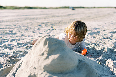 Toddler girl building a sand castle on the beach with her family - p1166m2212946 by Cavan Images