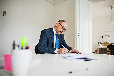 Mature businessman writing on documents at desk in office - p1185m1016011f by Astrakan