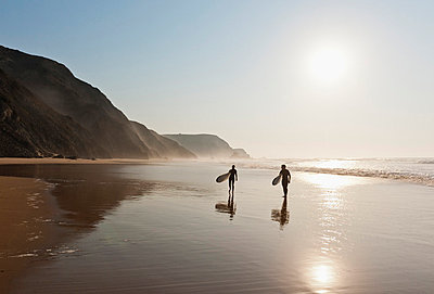 Couple walking with surfboard on beach - p300m730460f by Michael Reusse