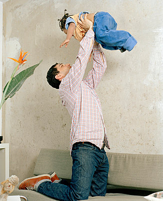 A man kneeling on a sofa and holding a toddler in the air - p3016665f by Paul Hudson