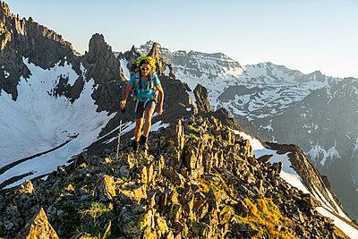 A Female Hiker Hiking On Blaine Peak Below Mount Sneffels In Colorado - p343m1223850 by Kennan Harvey