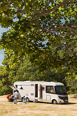 Mother and children unloading camper trailer parked against trees at trailer park - p426m2046437 by Maskot
