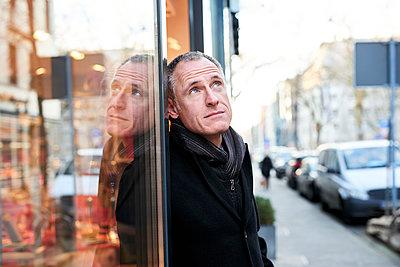 Mann in der Stadt vor einem Geschäft - p890m1217286 von Mielek
