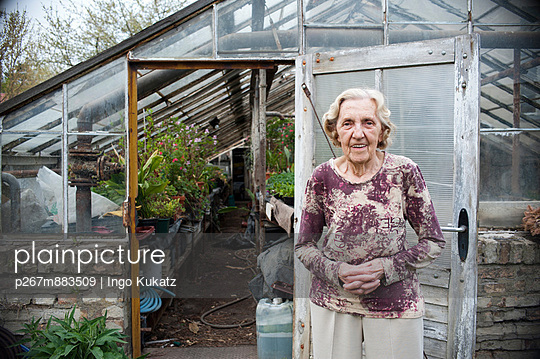 Old woman in front of a greenhouse - p267m883509 by Ingo Kukatz