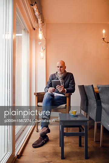 Senior man sitting at home, reading on digital tablet - p300m1587274 von Gustafsson