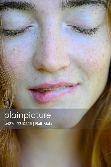 Young woman biting her lips - p427m2210826 by Ralf Mohr