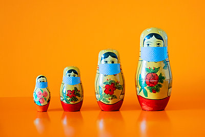 Four Russian Matryoshka dolls wearing surgical face masks - p1302m2181359 by Richard Nixon