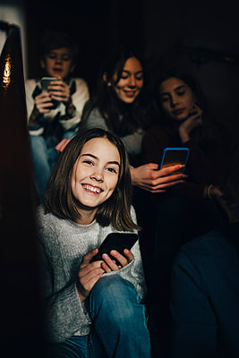 Portrait of smiling girl using mobile phone while sitting with friends on steps - p426m1555926 by Maskot