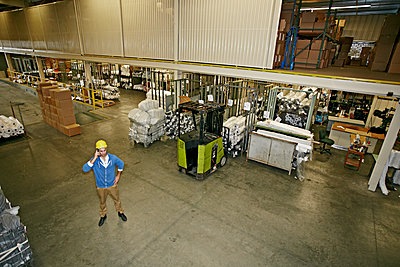 Caucasian worker talking on cell phone in warehouse - p555m1464270 by Peathegee Inc