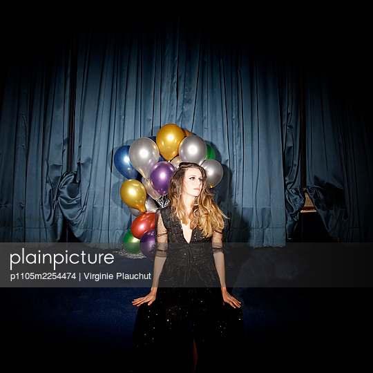 Young woman with bright balloons against stage curtain - p1105m2254474 by Virginie Plauchut