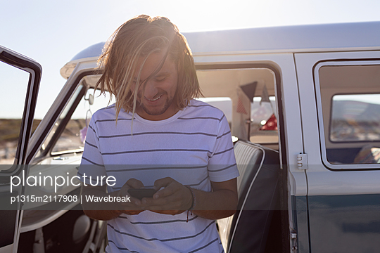 Young man using mobile phone near van at beach - p1315m2117908 by Wavebreak