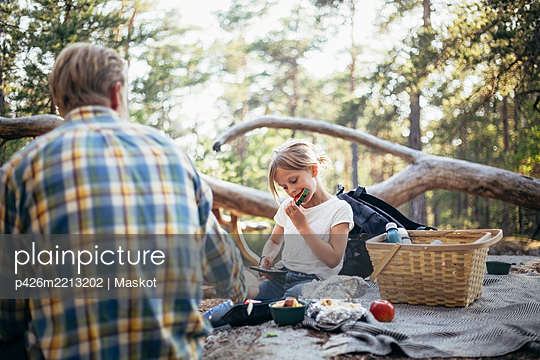 Daughter eating watermelon while sitting with father on picnic blanket in forest - p426m2213202 by Maskot
