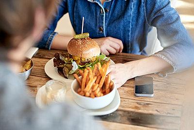 Junges Paar isst Hamburger und Pommes Frites - p1124m1564724 von Willing-Holtz