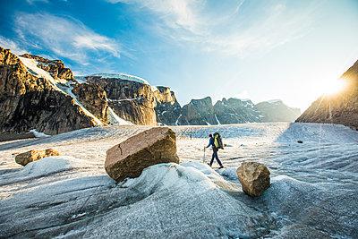 Mountaineer navigates glacier below mountains in Akshayak Pass. - p1166m2205810 by Cavan Images