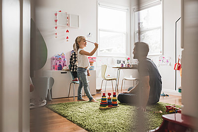 Father looking at daughters playing with toy in playroom at home - p426m1451759 by Maskot