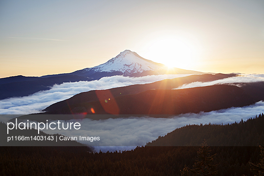 Scenic view of mountain covered with clouds during sunrise - p1166m1403143 by Cavan Images