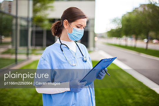 Female UK NHS doctor holding blue clipboard standing outside hospital clinic street entrance - p1166m2250564 by Cavan Images
