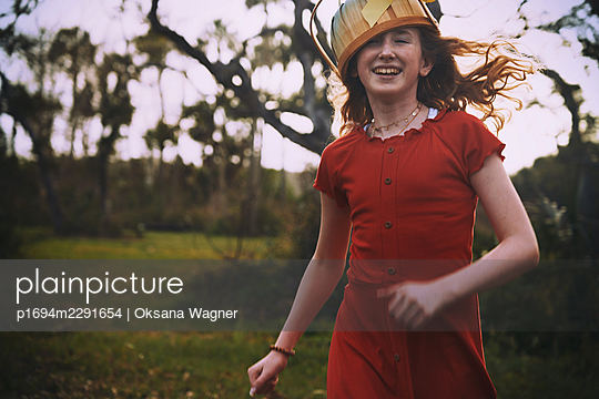 Red-haired girl wearing Easter basket as a headwear while running towards an Easter egg hunt  - p1694m2291654 by Oksana Wagner