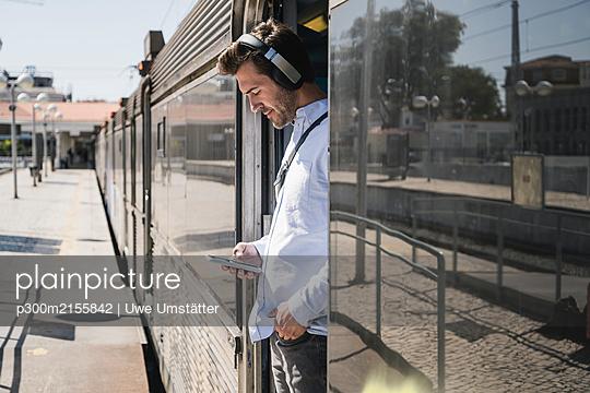 Young man with headphones and smartphone standing in train door - p300m2155842 by Uwe Umstätter