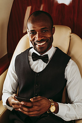 Smiling businessman holding mobile phone while sitting in private jet - p300m2256411 by OneInchPunch