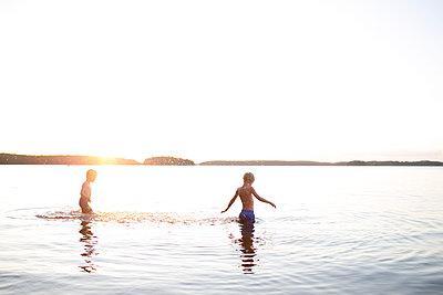 Boys walking in water - p312m1103669f by Fredrik Ludvigsson