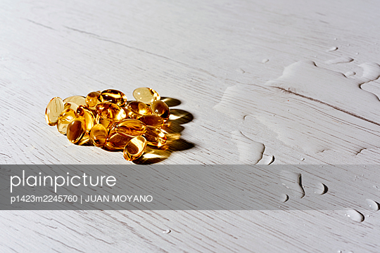 Some omega-3 fatty acid capsules and some water spilled on a white wooden table - p1423m2245760 von JUAN MOYANO