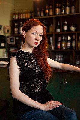 Schöne rothaarige Frau an der Bar - p045m1208457 von Jasmin Sander