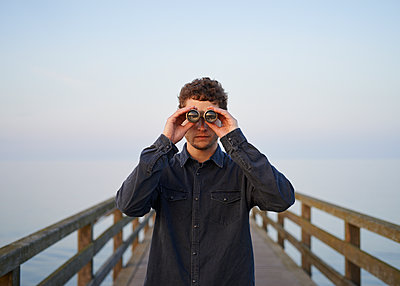 Man with binoculars - p1124m989086 by Willing-Holtz