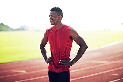 Tired male athlete standing with hands on hip at field - p1166m1088135f by John Trice