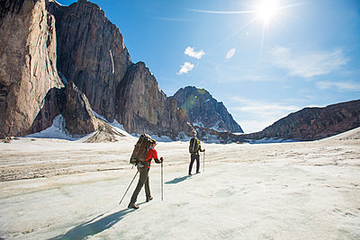 Two backpackers hiking on glacier below steep mountains. - p1166m2189736 by Cavan Images