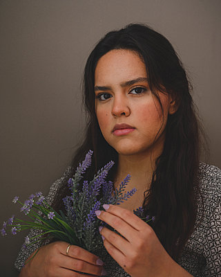 Portrait of a young beatiful hispanic woman on a grey background - p1166m2269212 by Cavan Images