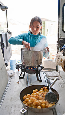 woman cooking for a hiking group in Iceland - p1166m2279424 by Cavan Images