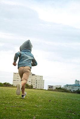 Junge mit Kapuze rennt durch einen Park - p1248m1526411 von miguel sobreira