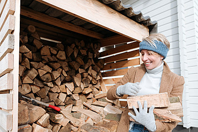 Portrait of smiling mature woman carrying firewood - p300m2170892 by Katharina und Ekaterina