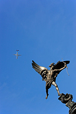 UK, London, Piccadilly Circus, airplane flying over the Eros sculpture - p300m978121f by Michael Zegers
