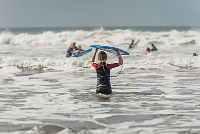 Boy carrying surfboard into the sea - p300m979087f by Andreas Pacek