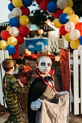 School aged boy dressed as Dracula Trick-or-Treating during Halloween - p1166m2208375 by Cavan Images