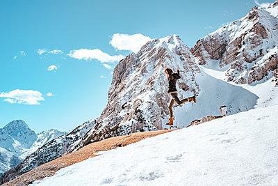 Young woman jumping at a mountain range in Kranjska Gora on a beautiful day - p1455m2077141 by Ingmar Wein