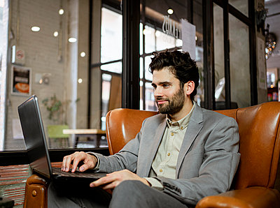 Smiling male entrepreneur working on laptop in cafe - p300m2277371 by Rafa Cortés
